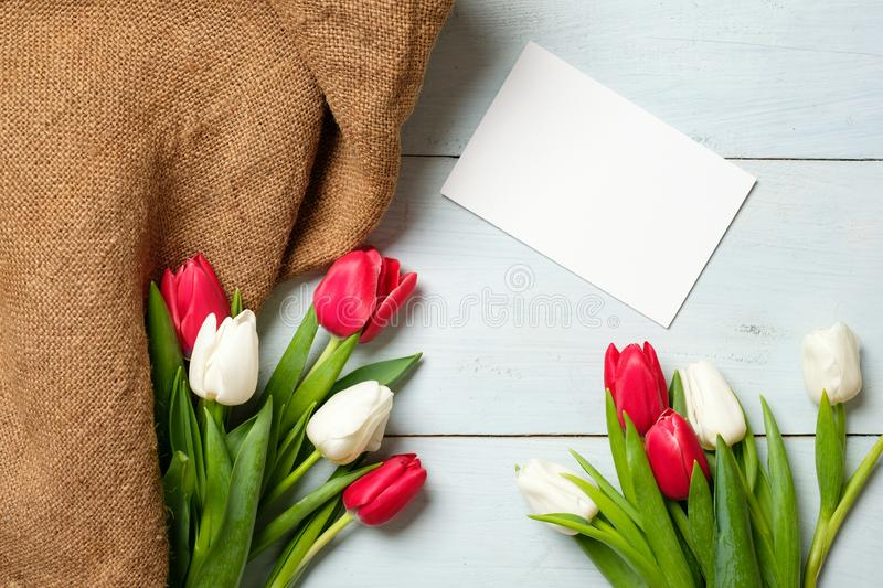 Bunch of tulips, burlap fabric and blank paper card on light blue wooden table. Banner mockup for easter, womans day, mothers day,. Spring holidays stock images