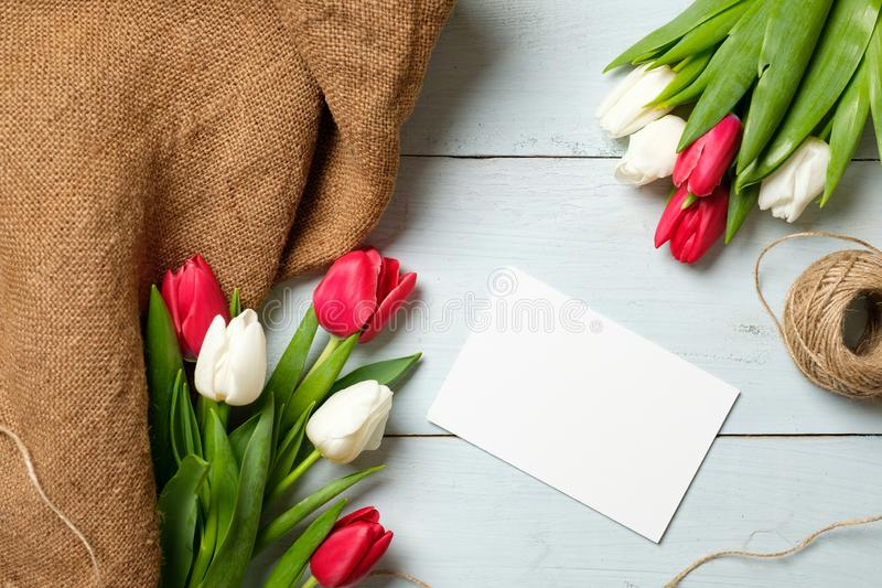 Bunch of tulips, burlap fabric and blank paper card on light blue wooden table. Banner mockup for easter, womans day, mothers day,. Spring holidays stock image