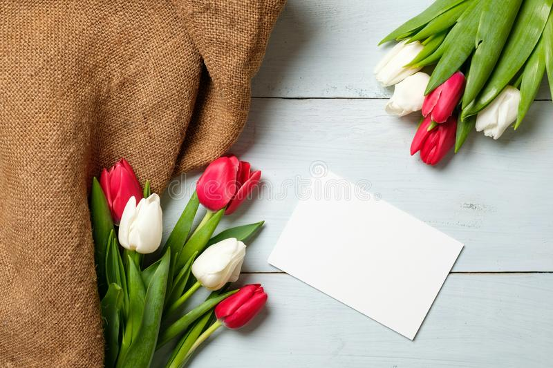 Bunch of tulips, burlap fabric and blank paper card on light blue wooden table. Banner mockup for easter, womans day, mothers day,. Spring holidays stock photos