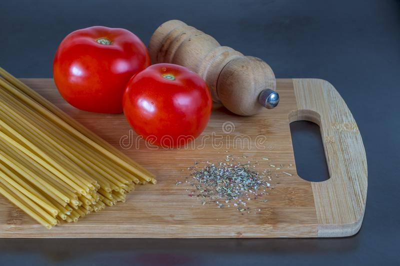 Bunch of uncooked whole wheat spaghetti pasta with tomatoes and spice on a cutting board royalty free stock photography