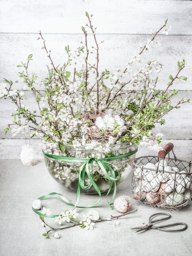 Bunch van lentebloesem in vaas met paaseieren op witte tafel Nog steeds leven Paasdecoraties royalty-vrije stock fotografie