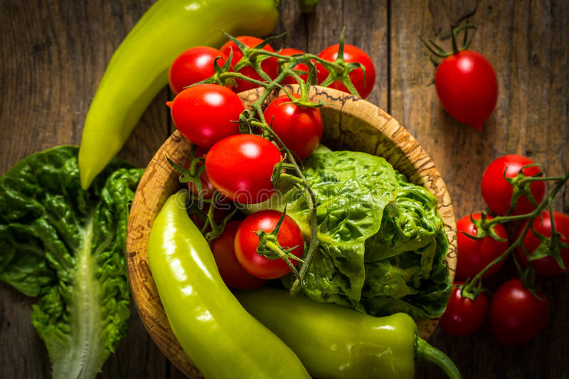Bunch of vegetables in the wooden bowl. Red tomato, yellow pepper and green salad stock image