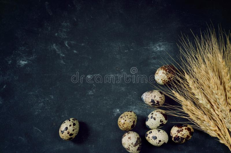 A bunch of wheat ears next to quail eggs on a black table, top view royalty free stock photography