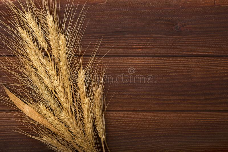 Bunch of wheat ears on the wooden table. Sheaf of wheat over wood background. stock photography