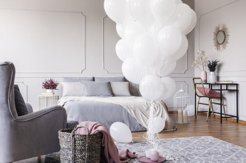 Bunch of white balloons in the middle of classy grey bedroom with elegant dresser with golden mirror, copy space on the empty wall. White balloons in the middle stock image