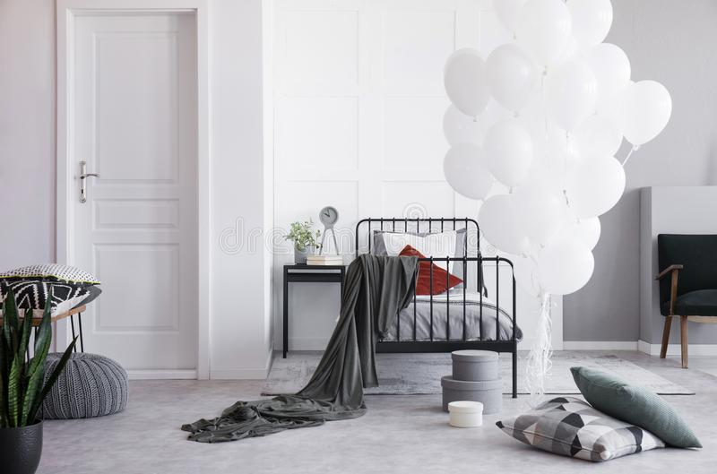 White balloons next to single metal bed with grey bedding and white and dark red pillows in bright scandinavian bedroom stock photography