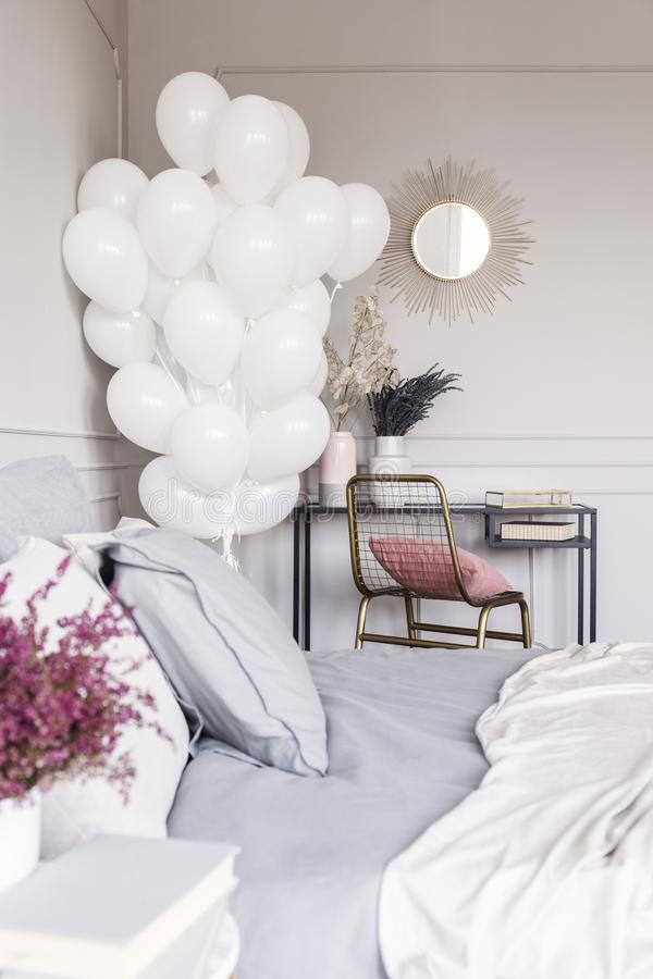 Bunch of white balloons in trendy bedroom interior with industrial dresser with golden mirror and bed with grey sheets. Bunch of balloons in trendy bedroom royalty free stock photography