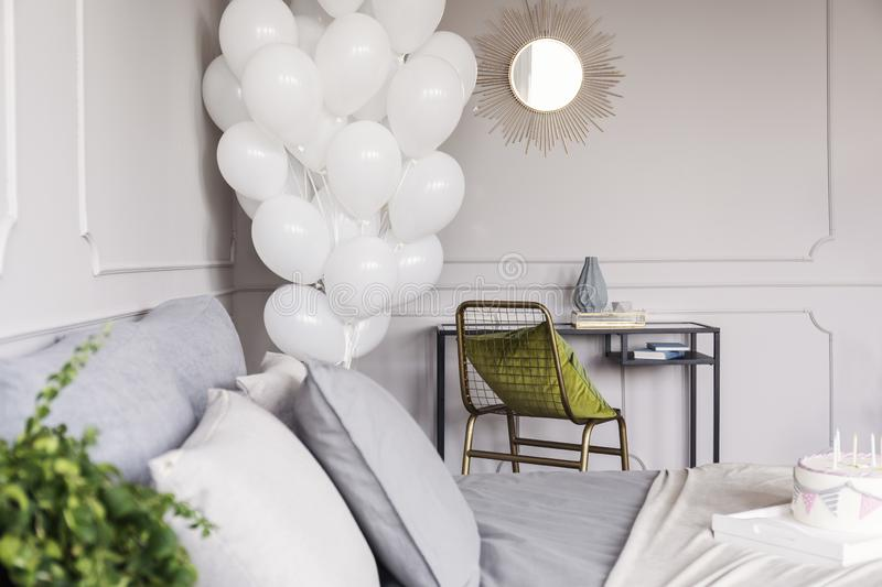 Bunch of balloons in trendy bedroom interior with industrial dresser with golden mirror and chair with green pillow and bed. Bunch of white balloons in trendy stock photo