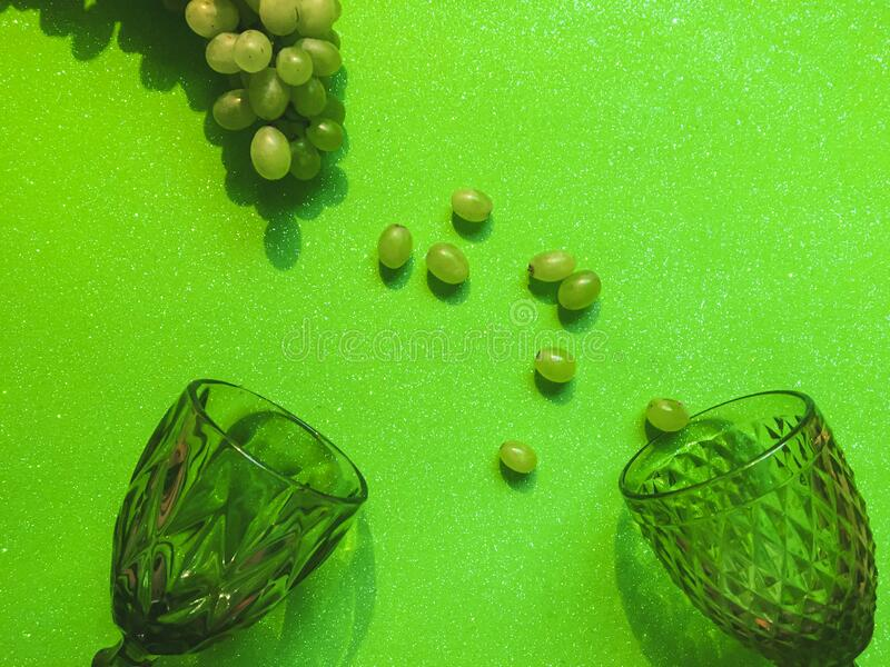 A bunch of white grapes and transparent green glsses. A bunch of white grapes and transparent green wine glasses on a green contrasting background and several stock image