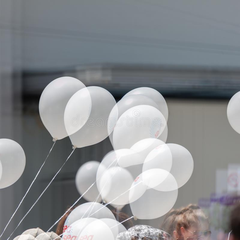 Bunch of white helium balloons on strings at an outdoor event, with double exposure stock image