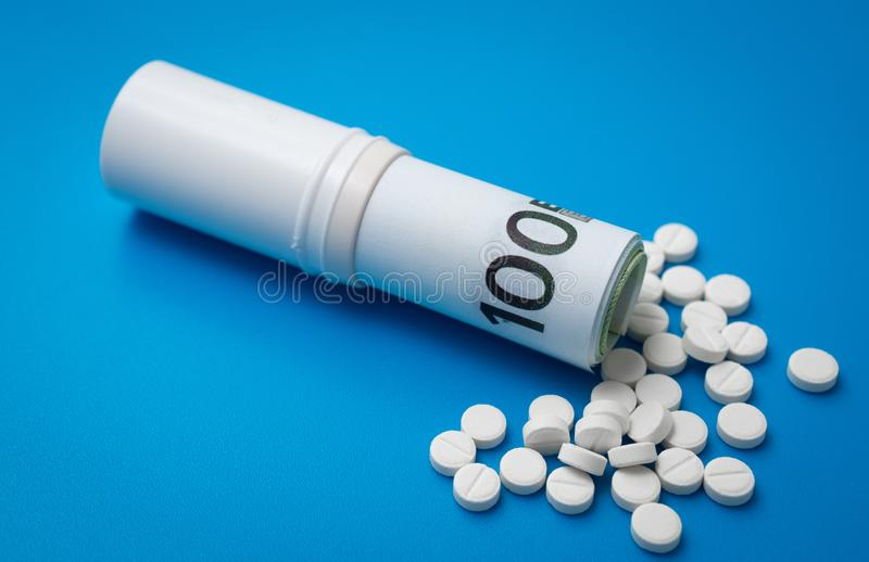 Bunch of white tablets with banknotes. Pharmaceutical business royalty free stock photos