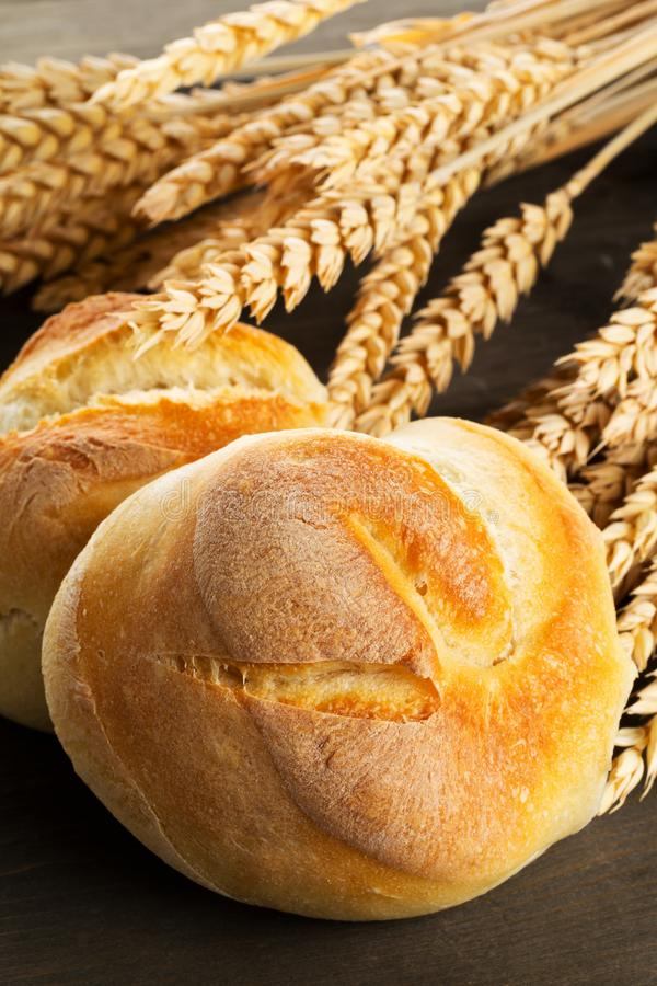 Bunch of whole, fresh baked wheat buns with wheat ears on dark w stock images