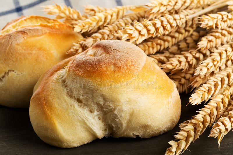 Bunch of whole, fresh baked wheat buns with wheat ears on dark w royalty free stock photo