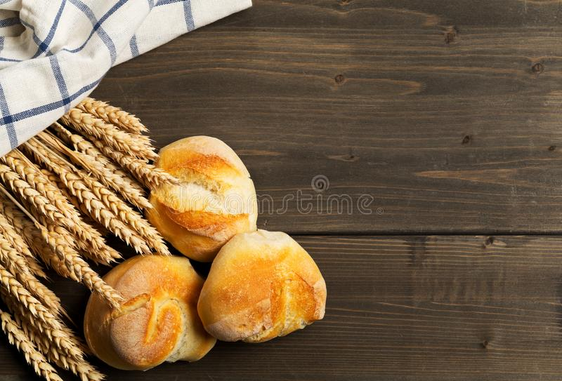 Bunch of whole, fresh baked wheat buns with wheat ears on dark w stock photos