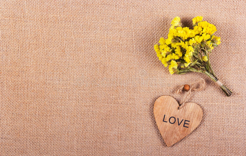 A bunch of yellow flowers and a wooden heart on a natural linen background. Romantic concept. stock photos