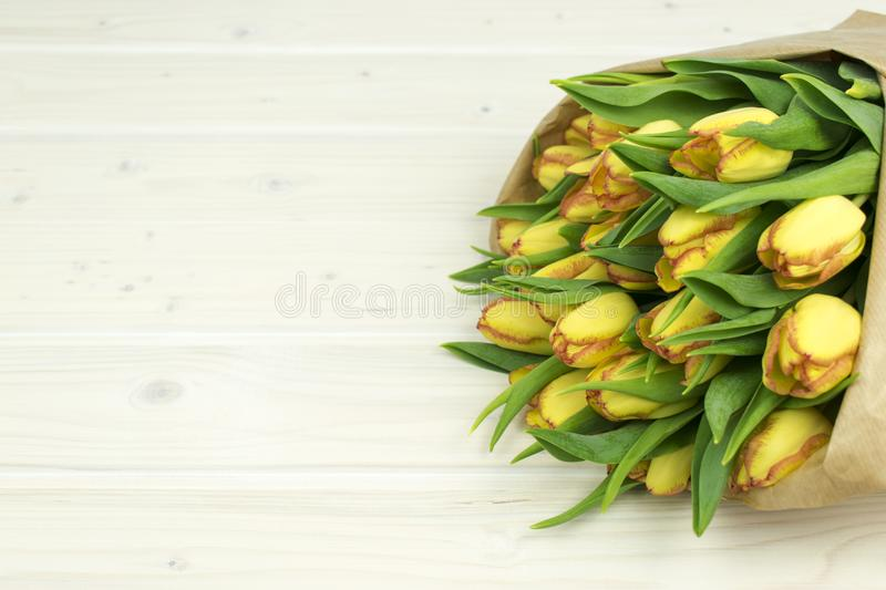 Bunch of yellow tulips on a wooden table wraped in paper royalty free stock image