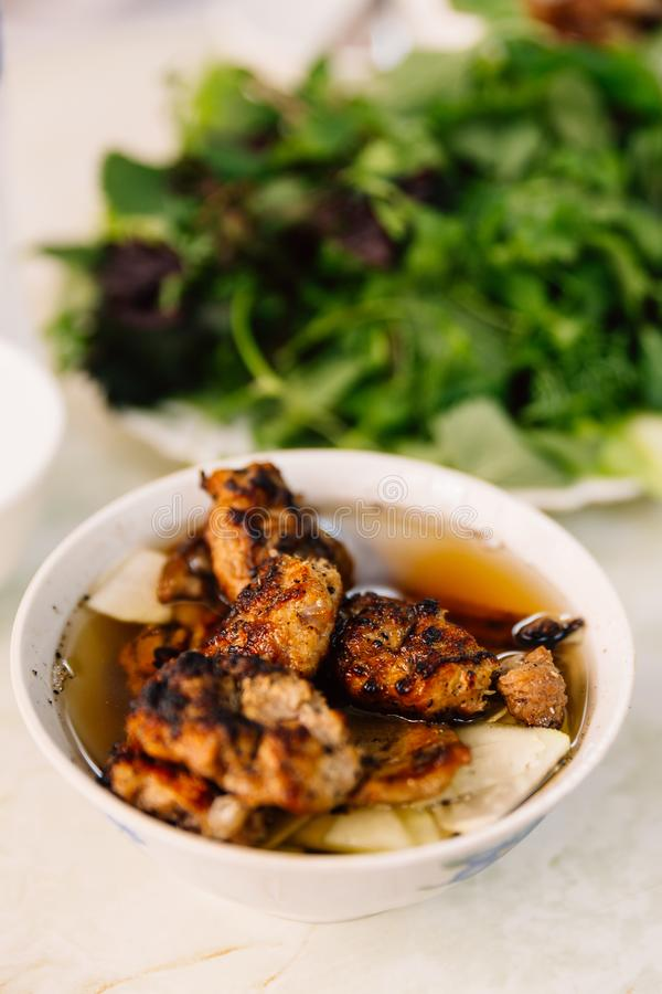 Buncha is a Vietnamese dish of grilled pork and noodle served with vegetables at the restaurant in Hanoi, Vietnam royalty free stock images