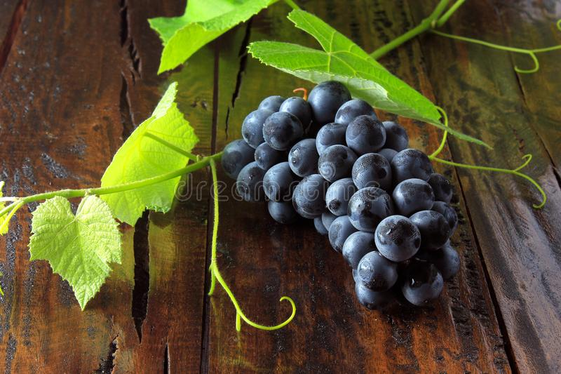 Bunches of fresh grapes with branches and leaves on rustic wooden table stock photos