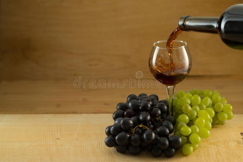 Bunches of grapes and a glass of wine on a wooden background royalty free stock photo