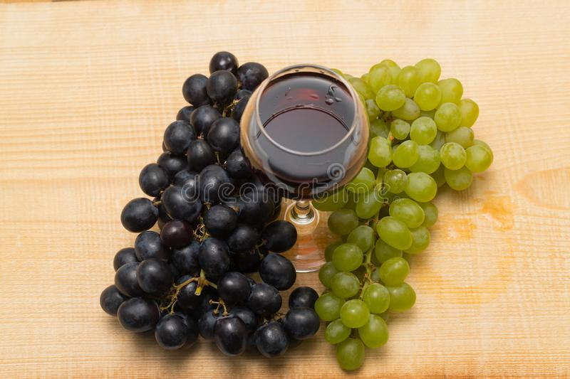 Bunches of grapes and a glass of wine on a wooden background stock photos