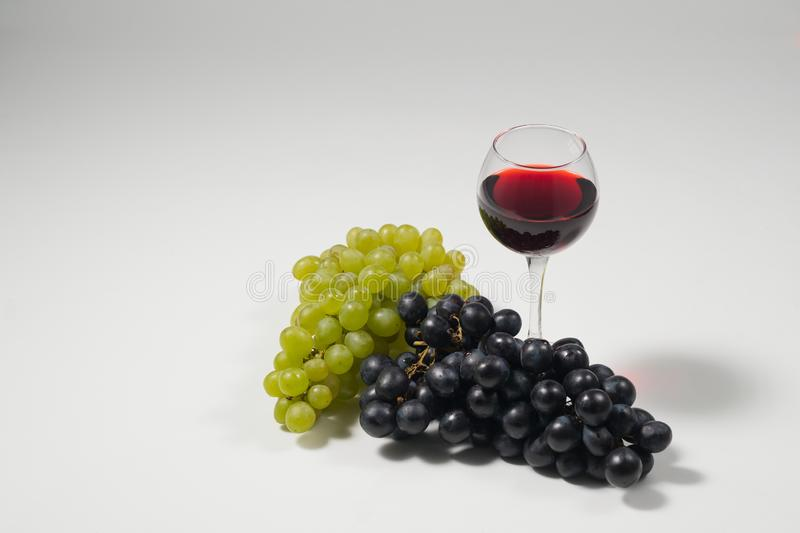 Bunches of grapes and glasses of wine on a white background royalty free stock photo