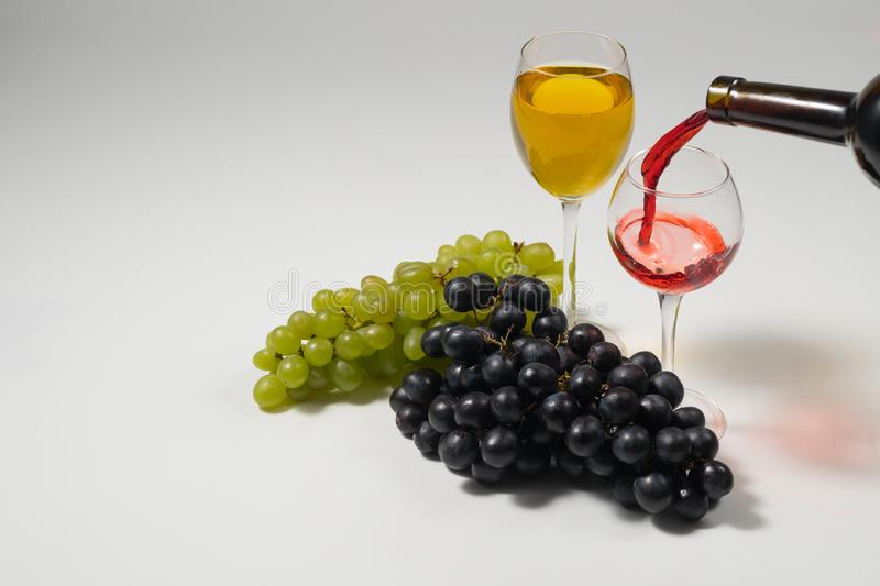 Bunches of grapes and glasses of wine on a white background stock image
