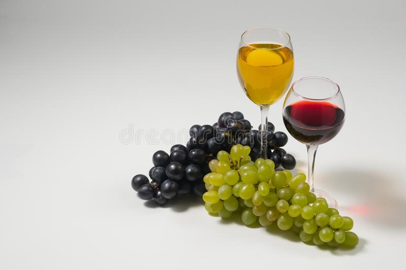 Bunches of grapes and glasses of wine on a white background royalty free stock image
