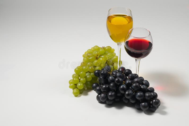 Bunches of grapes and glasses of wine on a white background royalty free stock images