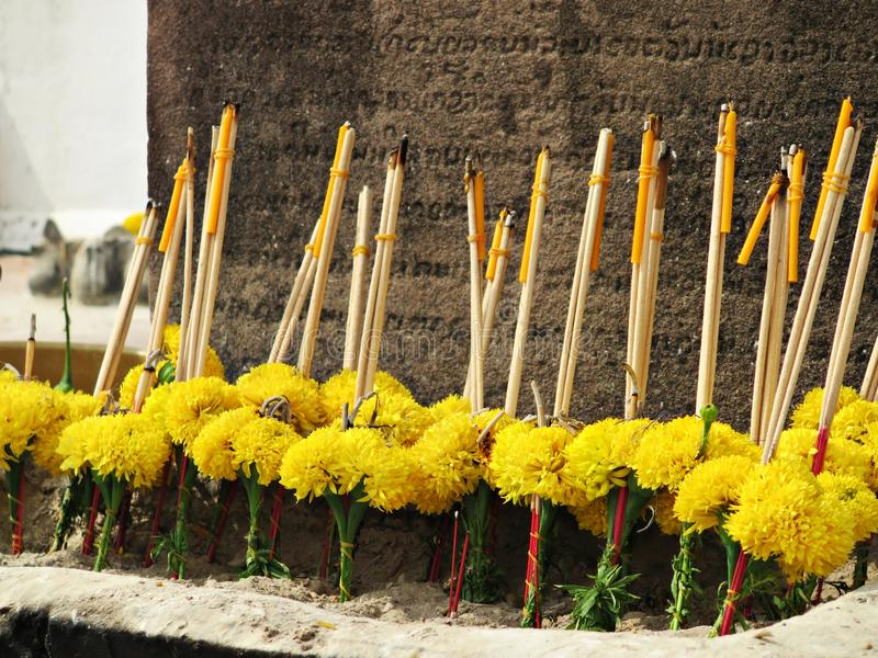 Bunches of marigold flowers with joss sticks and candles stock image