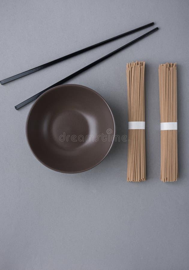 Bundels van Soba-Zwarte het Bamboeeetstokjes van de Noedels Donkere Lege Kom op Grey Background Japanse Chinese Aziatische Keuken royalty-vrije stock fotografie