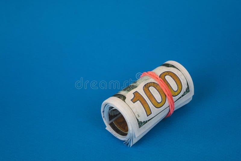 bundels van verdraaid geld van verschillende munten op een blauwe achtergrond stock afbeelding