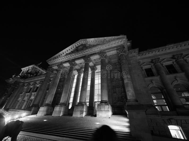 Bundestag parliament in Berlin at night in black and white. Bundestag German Houses of Parliament in Berlin, Germany at night. Dem deutschen Volke means To the royalty free stock photo