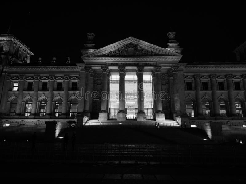 Bundestag parliament in Berlin at night in black and white. Bundestag German Houses of Parliament in Berlin, Germany at night. Dem deutschen Volke means To the stock photography