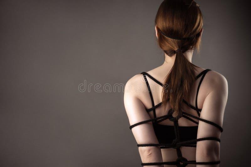 Bundet med den sexiga kvinnan för rep, träldom royaltyfri bild