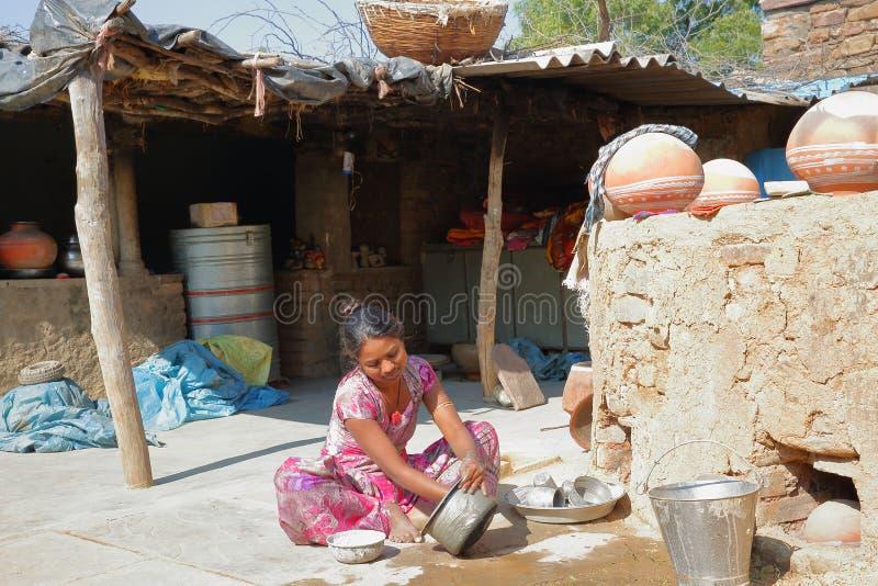 BUNDI, РАДЖАСТХАН, ИНДИЯ - 9-ОЕ ДЕКАБРЯ 2017: Портрет красивой молодой женщины моя блюда в дворе фермы внутри стоковые изображения rf