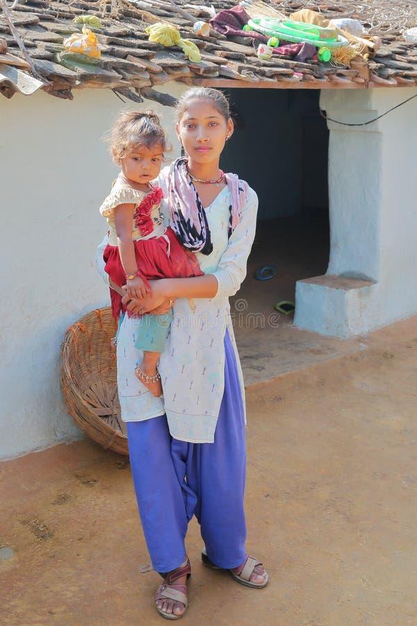 BUNDI, РАДЖАСТХАН, ИНДИЯ - 9-ОЕ ДЕКАБРЯ 2017: Портрет красивой молодой женщины при ее младенец представляя в дворе фермы i стоковое фото rf