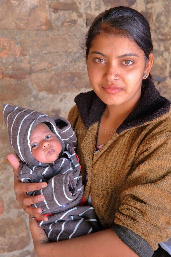 BUNDI, РАДЖАСТХАН, ИНДИЯ - 9-ОЕ ДЕКАБРЯ 2017: Портрет красивой молодой женщины с ее младенцем в деревне близко к Bundi стоковые изображения