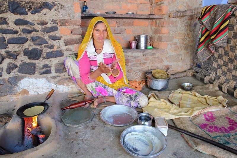 BUNDI, РАДЖАСТХАН, ИНДИЯ - 9-ОЕ ДЕКАБРЯ 2017: Портрет красивой молодой женщины подготавливая хлеб chapati плоский в дворе o стоковое фото rf
