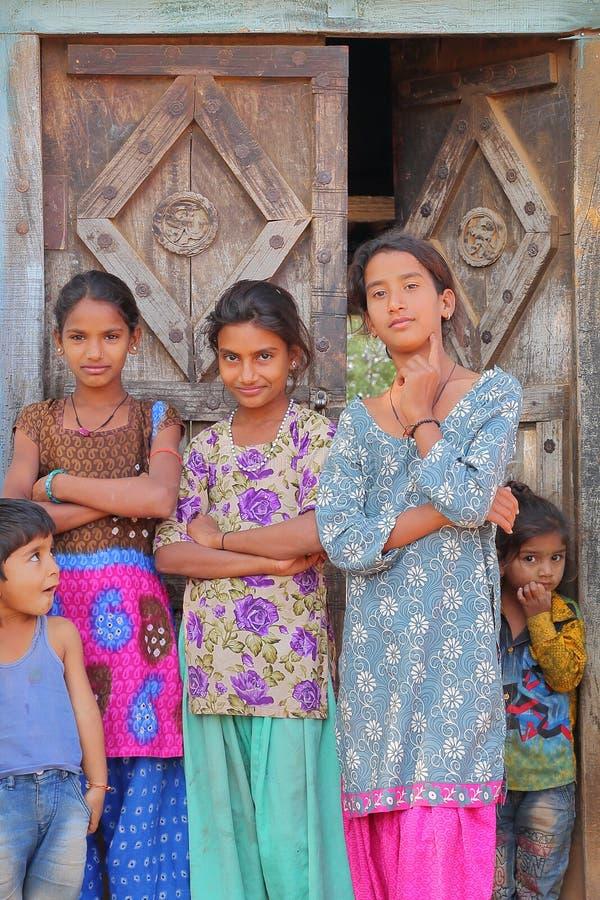 BUNDI, RAGIASTAN, INDIA - 9 DICEMBRE 2017: Un ritratto di tre adolescenti e di due bambini che posano all'entrata di una casa den fotografia stock