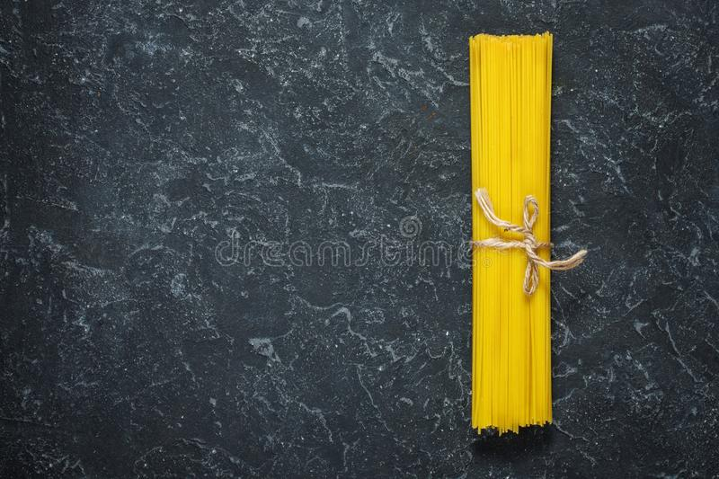 Bundle of Italian spaghetti pasta tied with string lying on dark stone background stock photography