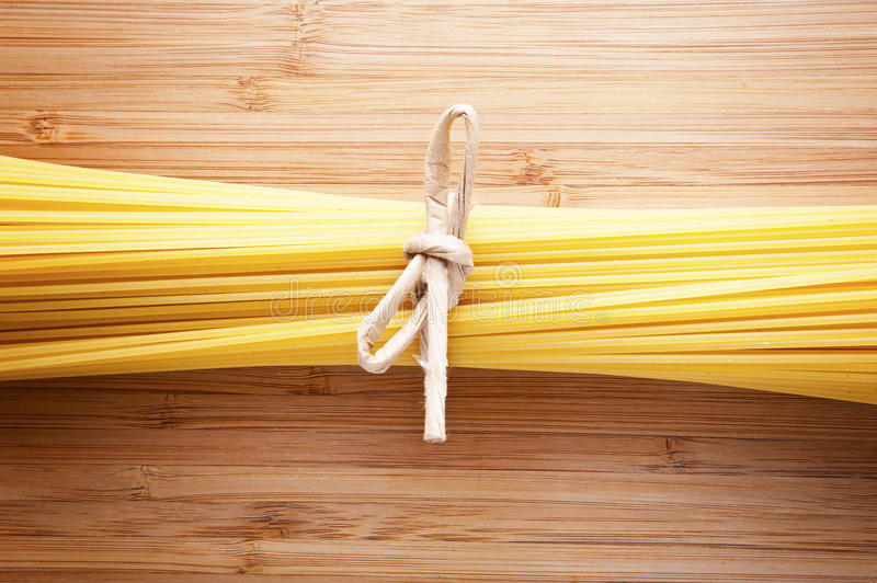 Bundle of Italian spaghetti pasta tied with string lying on old royalty free stock photo