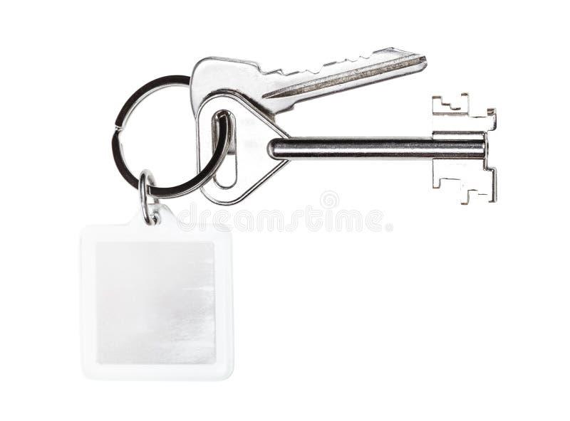 Bundle of keys with blank keychain isolated. Bundle of keys on keyring with blank keychain isolated on white background stock images