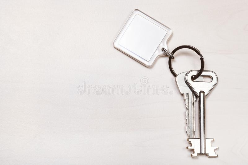 Bundle of keys on ring with blank white keychain. Bundle of keys on keyring with blank white keychain on pale brown table stock image