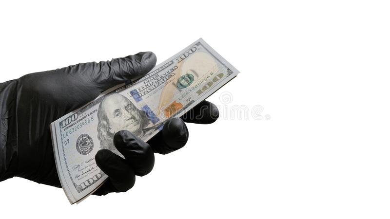 A bundle of US dollars in a male hand in a black glove. Object for the design of the concept of violation of the law, corruption, royalty free stock photos