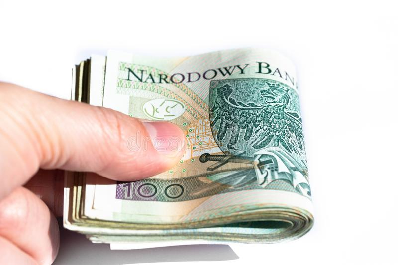 Bundle of 100 zloty banknotes in the hand of a young man. Close up. stock image