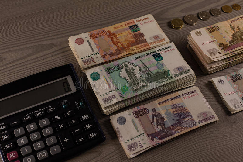 Bundles of money. Russian rubles and calculator on a wooden background. royalty free stock images