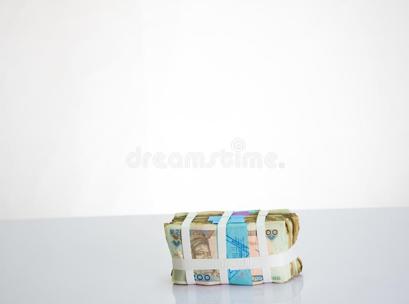 Bundles of Naira Cash local currencies in white strap against white background. Bundles of N200 Naira Cash local currencies in white strap against white stock photos