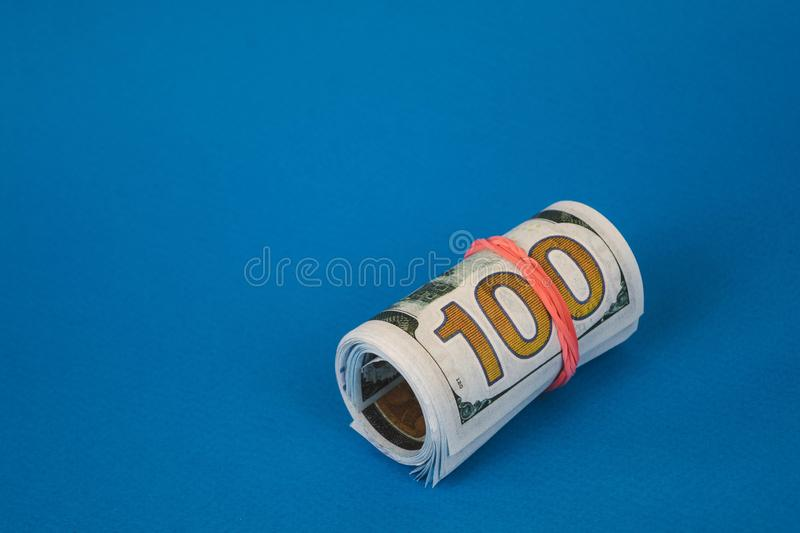 bundles of twisted money of different currencies on a blue background stock image
