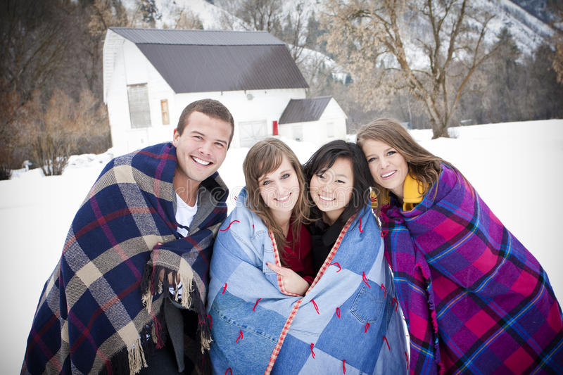 Bundling Up for the Cold Winter Weather. A group of Friends huddle together and bundle up with warm blankets on a cold winter day. Ethnically diverse group royalty free stock photo
