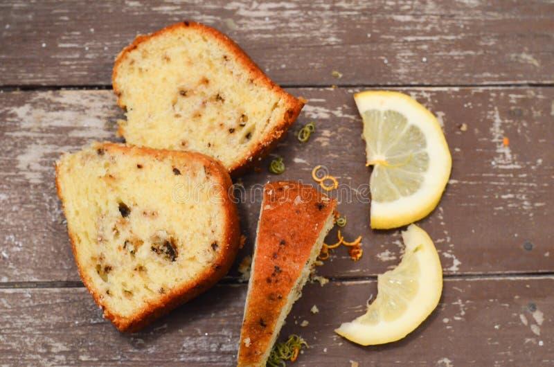 Bundt lemon cake. Slice of moist lemon bundt cake with real lemons in background stock photos
